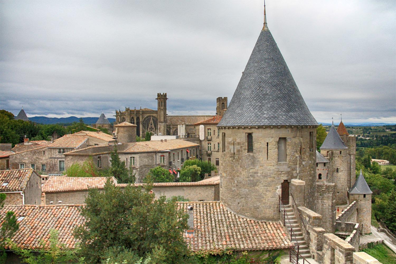 Op de achtergrond de Basilique Saint-Nazaire. Rechtsvoor een van de vele ronde torens. Bij de restauratie koos architect Viollet-le-Duc voor leisteen, wat echter in deze regio niet echt gebruikelijk is. Dat kwam hem in de loop der tijd op veel kritiek te staan.