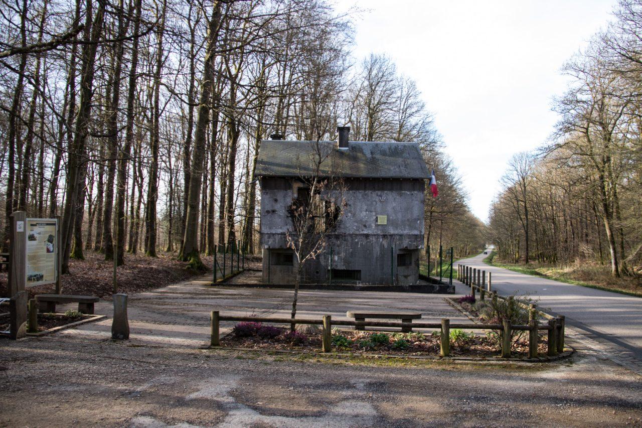 Langs de kant van de weg, vlakbij de Belgische grens, een versterkt huis uit de Tweede Wereldoorlog, met kogelgaten.